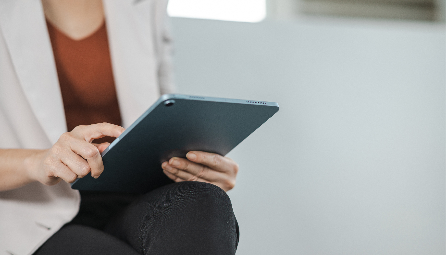A woman in a white blazer using a tablet computer.